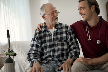 Cheerful elderly man with a nasal tube speaking with a male nurse at his hospital bed.