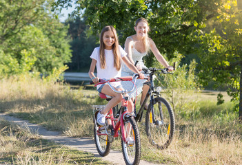Happy smiling girl riding bicycle with young mother in field at hot summer day