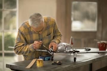 Senior man repairing the propeller of a toy airplane on a workbench in his garage.