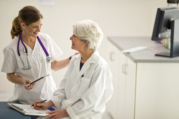 Smiling nurse and a female doctor having a discussion inside an exam room.