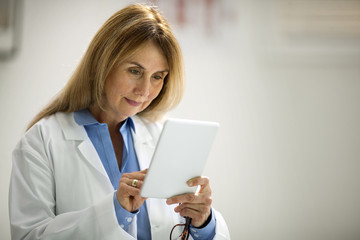 Mid adult doctor using a digital tablet.