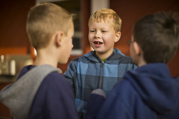 Smiling boy talking with his friends outdoors