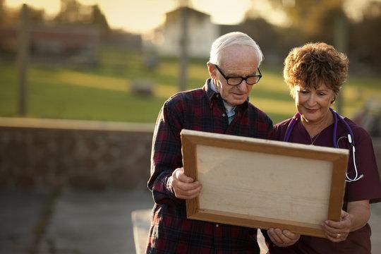 Mature nurse and senior man admiring a piece of art.