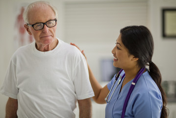 Smiling female nurse comforting an elderly male patient.