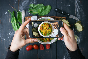 Phone photography of food. Woman hands take photo of lunch with smartphone for social media. Quinoa salad. Raw vegan vegetarian healthy dinner