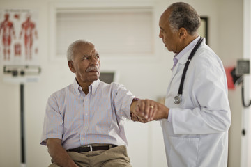 Senior man having his arm examined by a male doctor inside a doctor's office.