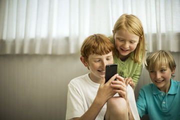 Smiling young siblings playing with a smart phone.
