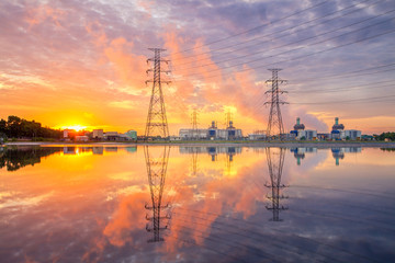 The sun is rising behind a power plant.