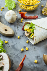 Vegan burrito from vegetables, mushrooms and tortillas. On a gray table among the ingredients