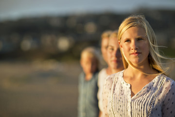 Portrait of a teenage girl standing on a beach with her family.