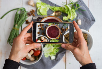 Phone photography of food for social networks. Smartphone photo of beetroot soup. Russian traditional borscht. Raw vegan vegetarian healthy food