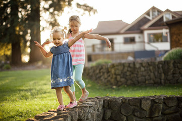 Two sisters playfully balancing on a stone wall.