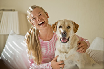 Happy young woman laughs as she hugs her dog in her sunlit bedroom.