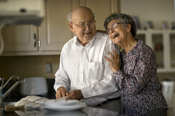 Smiling elderly couple share an affectionate moment while they do the dishes together.