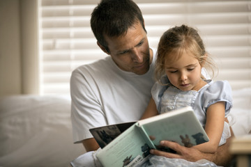 Father and daughter reading story book at home