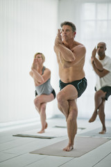 Mature man concentrates on his difficult pose as he attends a yoga class.