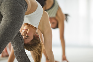 Young woman concentrates on her pose as she attends a yoga class.