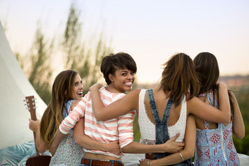 Friends hugging on a balcony