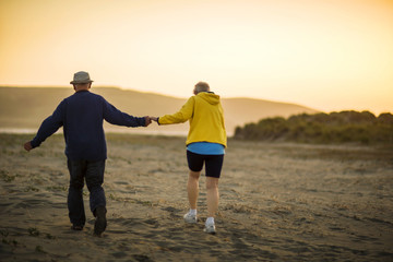 Elderly couple enjoy going for a walk together along the beach at sunset.