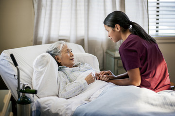 Friendly young nurse sits on an elderly patient's bed to chat with them.