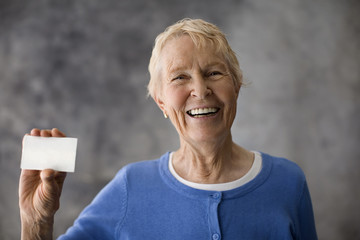 Senior woman holding up a white card.