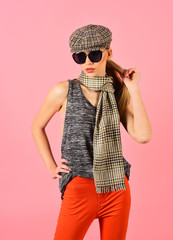 Slim blond model in tartan cap and scarf wearing big black sunglasses isolated on pink background