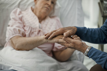 Close up of senior man holding hands on sick wife