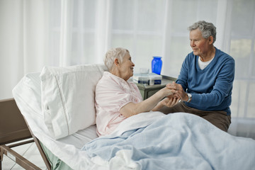 Senior man holding hands with his ailing wife.