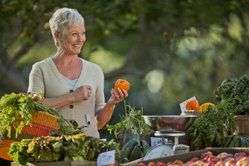 Mature woman shopping for fresh vegetables at a farmer's market.