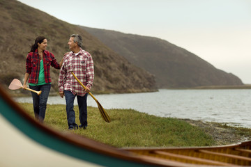 Mature couple talking with each other and walking towards canoe near river