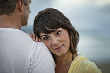 Portrait of a middle aged woman leaning on her partner's shoulder.