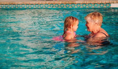 grandmother teaching little granddaughter to swim