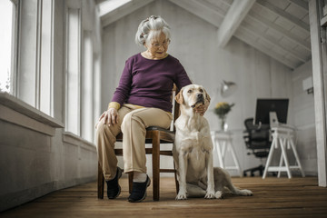 Senior woman sitting pensively with her dog by her side.