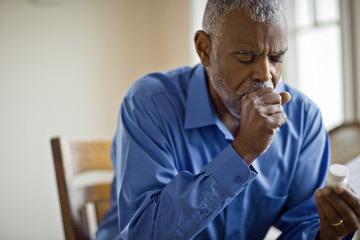 Sick man looks at pill bottle whilst coughing