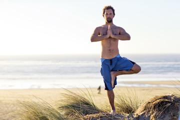 Man in yoga pose at beach.