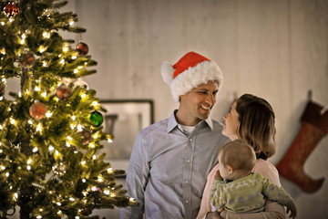 Couple and their baby standing next to the Christmas tree.