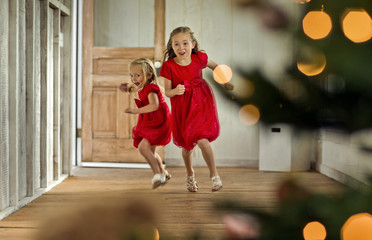 Two excited young girls run towards the Christmas tree.