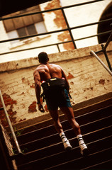 Rear view of an athletic man climbing up the stairs.