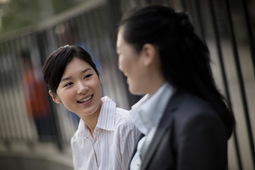 Smiling young businesswoman speaking with a colleague.