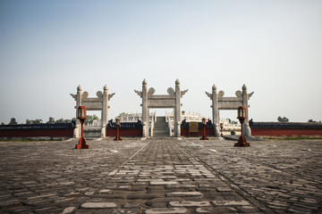 Three traditional gates in a paved courtyard.