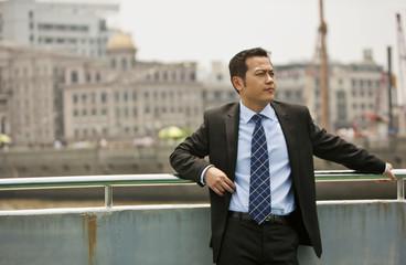 Businessman leaning against railing.