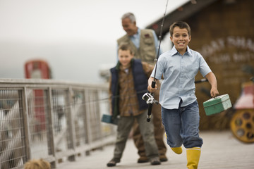 Exited boy running down a wharf carrying fishing gear with his father and brother
