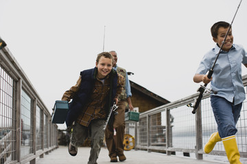 Exited brothers running down a wharf carrying fishing gear with their father.