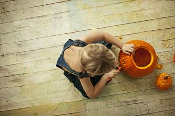 Little boy carving Halloween pumpkin