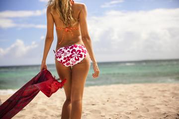 Young woman in a bikini walking towards the sea.