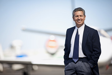 Businessman standing in front of a private jet and smiling