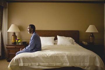 Man sitting on a bed looking thoughtful.