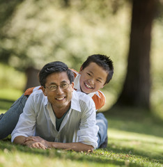 Portrait of a smiling father and his young son lying in the park.
