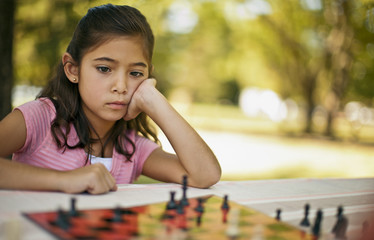 Bored young girl watching a game of chess at the park.