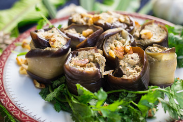 Roasted eggplant rolls with walnuts, garlic, coriander, oil, onion. Traditional Georgian food cold snack. Rolls for dinner or lunch. Raw vegan vegetarian healthy food